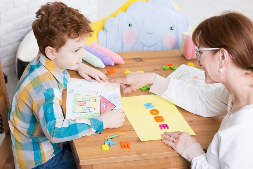 woman ABA therapist with dark red hair performing ABA therapy with a young boy with dark red hair