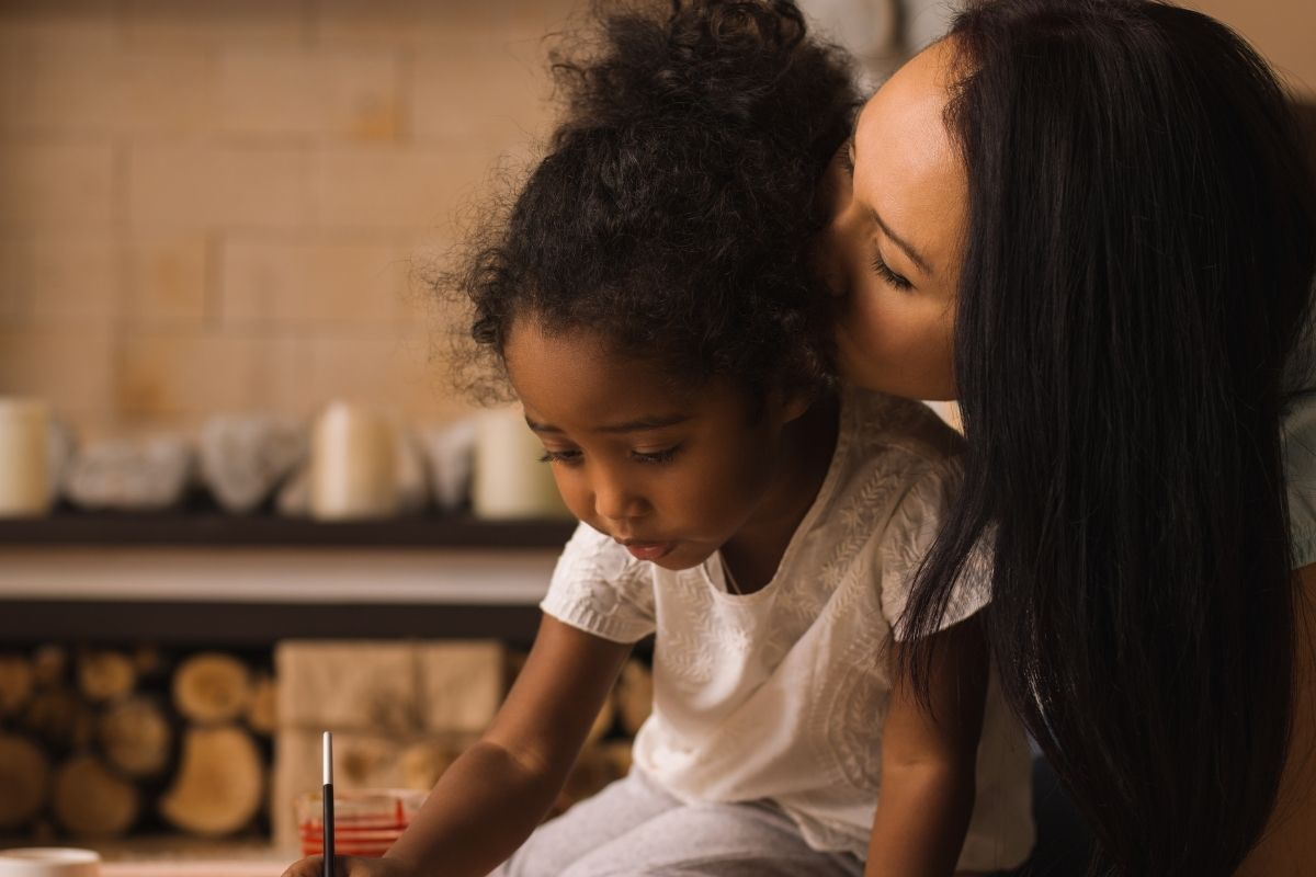 brown skinned woman kissing her brown skinned child who is painting